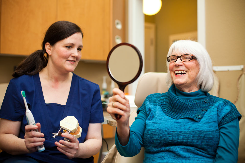 A dental assistant with a patient holding mirror and smiling.